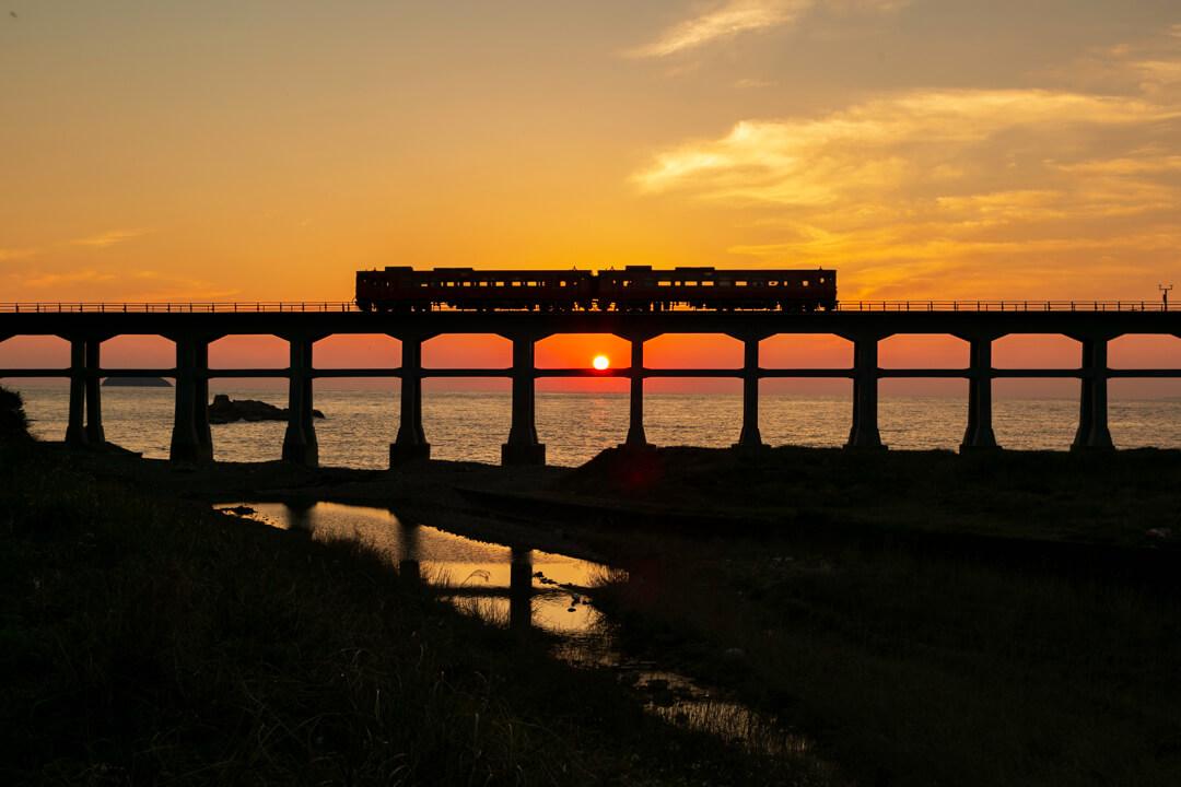 惣郷川橋梁と夕日の写真