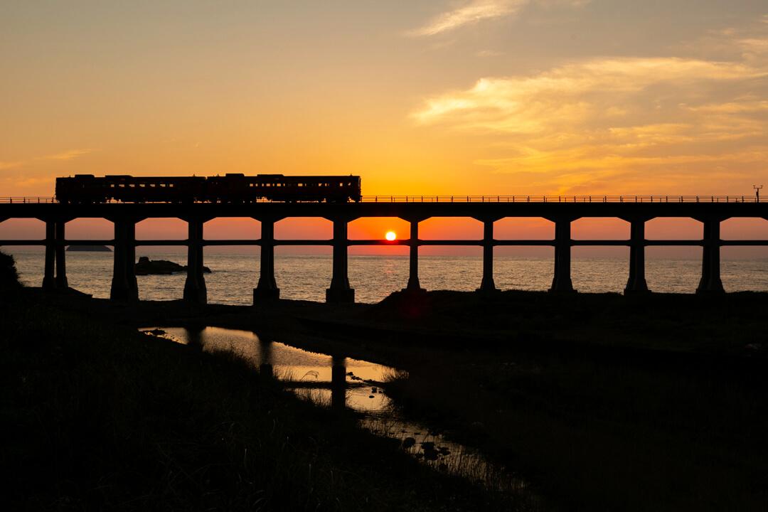 夕日を背に走る列車と惣郷川橋梁の写真