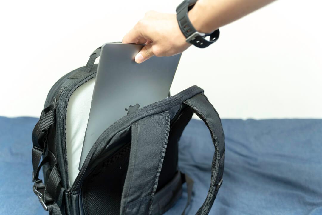 Amazonベーシックのカメラバッグ(22.8L)の背面ポケットにノートパソコンを収納する様子
