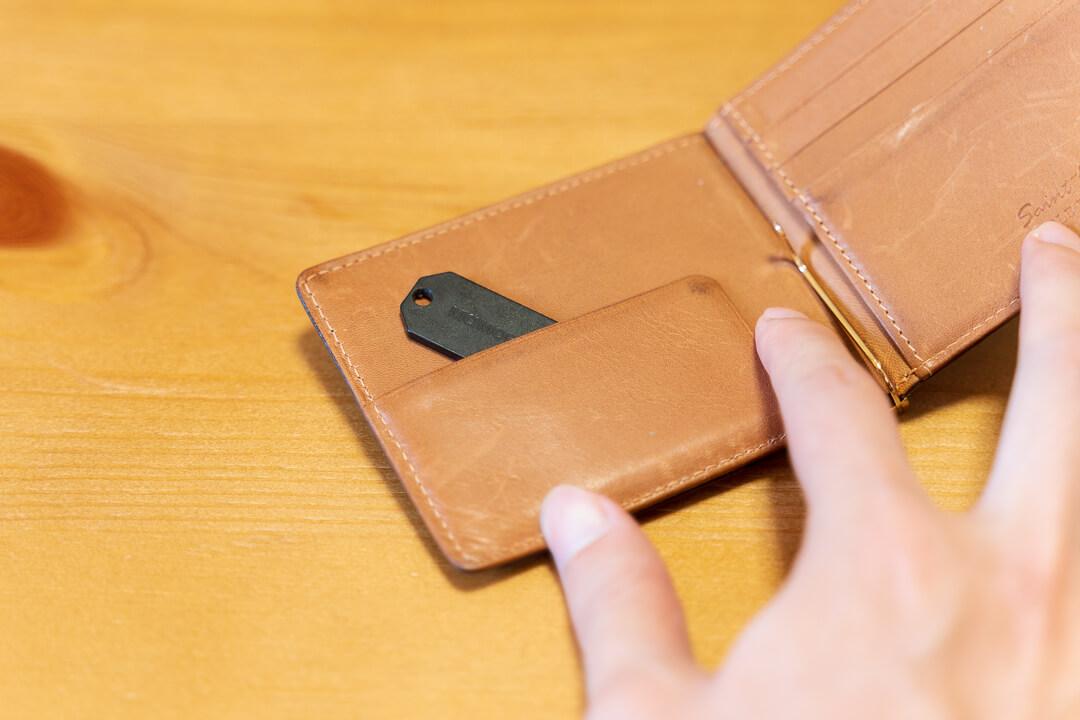 紛失タグ(スマートタグ)を財布に挟む様子