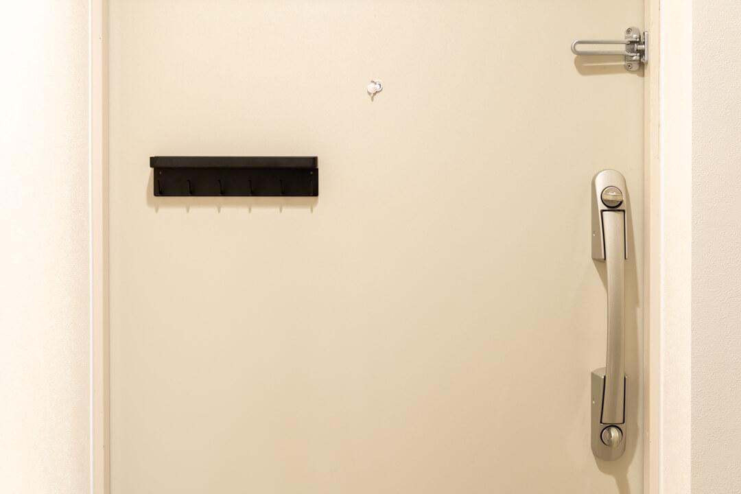 マグネットキーフック&トレイを玄関ドアにつける様子